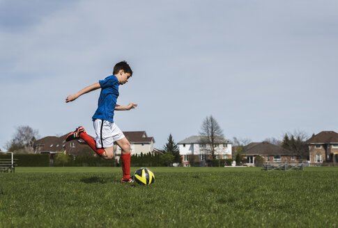 Side view of boy kicking soccer ball while playing on grassy field - CAVF50325