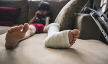 Boy with fractured leg sitting on sofa at home - CAVF50337