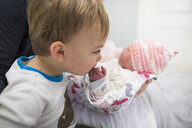 Cute brother kissing newborn sister's hand carried by mother at home - CAVF50373