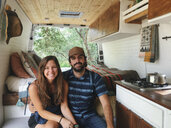 Portrait of happy couple sitting in motor home at forest - CAVF50382