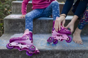 Low section of mother assisting daughter in wearing roller skates while sitting on steps - CAVF50421