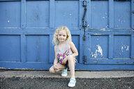 Portrait of girl crouching by blue door - CAVF50442