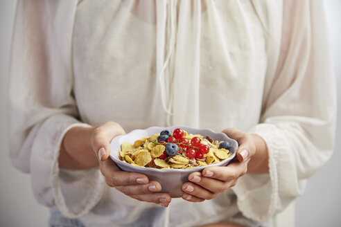 Midsection of woman having breakfast in bowl while standing at home - CAVF50463