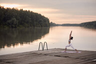 Woman practicing warrior 1 pose on pier by lake against cloudy sky during sunset - CAVF50466