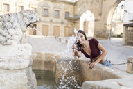 Spain, Baeza, smiling young woman splashing with water of a fountain - JASF01969