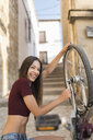 Spain, Baeza, portrait of laughing young woman repairing her bicycle with wrench - JASF01972