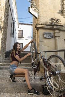 Spain, Baeza, smiling young woman repairing her bicycle - JASF01975