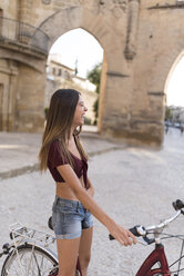 Spain, Baeza, laughing young woman with bicycle in the city - JASF01978