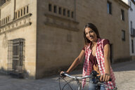 Spain, Baeza, portrait of smiling young woman with bicycle - JASF01981