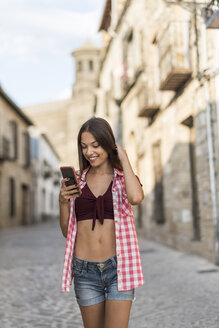 Spain, Baeza, smiling young woman looking at cell phone - JASF01984