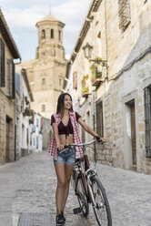 Spain, Baeza, smiling young woman with bicycle in the city - JASF01987