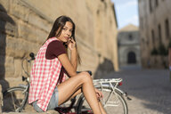 Spain, Baeza, portrait of young woman with bicycle resting at sunlight - JASF01990