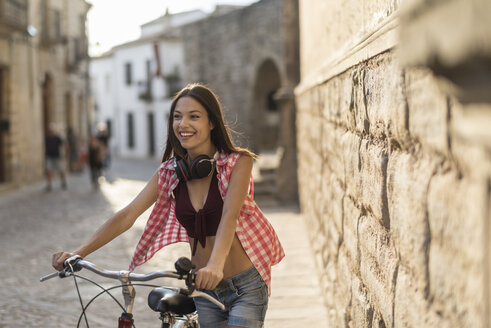 Spain, Baeza, portrait of happy young woman pushing her bicycle in the city - JASF01993