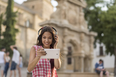 Spain, Baeza, portrait of smiling young woman using headphones and digital tablet in the city - JASF01996