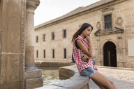 Spain, Baeza, pensive young woman sitting on edge of fountain - JASF01999