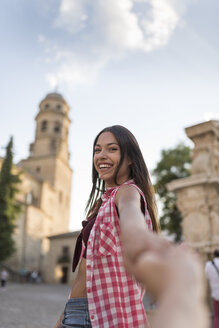 Spain, Baeza, portrait of happy young woman holding hands in the city - JASF02002