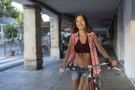 Spain, Baeza, portrait of laughing young woman with bicycle - JASF02008