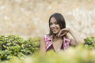 Spain, Baeza, portrait of smiling young woman relaxing in public park - JASF02014