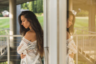 Serious brunette young woman at a window outdoors - KKAF02474