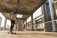 Young man riding skateboard in the city - KKAF02483