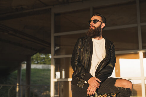 Stylish bearded young man outdoors looking sideways - KKAF02489