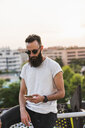 Cool bearded young man wearing sunglasses checking cell phone - KKAF02504