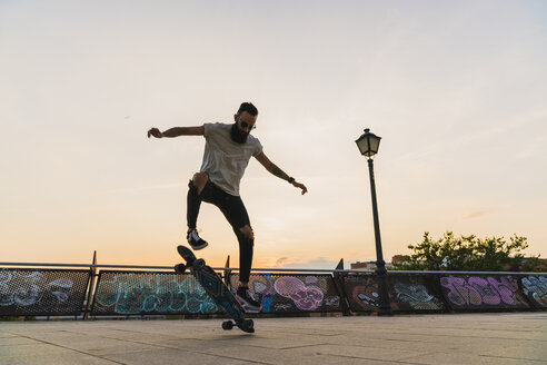 Young man doing a skateboard trick in the city at sunset - KKAF02516