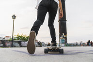 Close-up of young woman riding skateboard in the city - KKAF02519