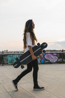 Young woman walking with skateboard in the city - KKAF02522
