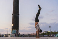 Young man doing a handstand in the city at sunset - KKAF02528