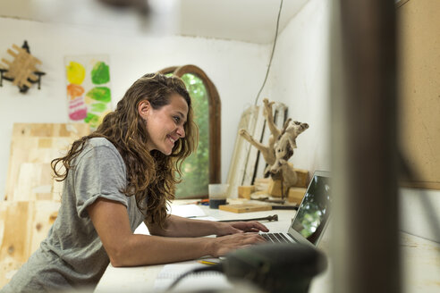 Craftswoman using laptop at her desk - JPTF00033