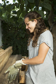 Smiling craftswoman putting on protective gloves at a pile of wood - JPTF00036