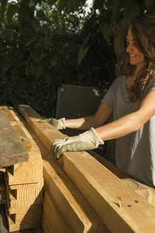 Smiling craftswoman wearing protective gloves working with wood - JPTF00039