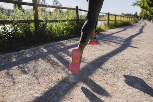 Legs of sportive woman running on path - FMOF00385