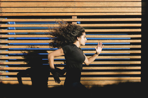 Sportive young woman running along wood paneling - FMOF00388