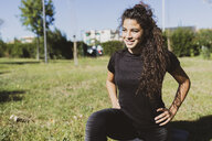Sporty young woman exercising on a meadow - FMOF00391