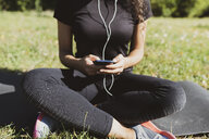 Sporty young woman having a break on a meadow using cell phone - FMOF00394