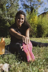 Sporty young woman stretching her leg on a meadow - FMOF00397