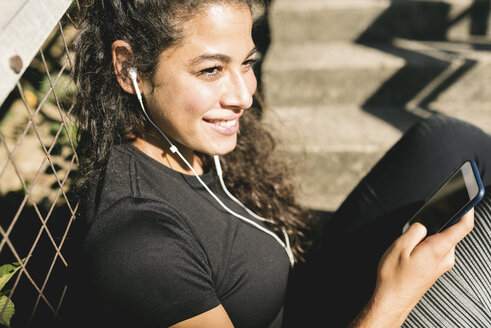 Sporty young woman having a break listening to music - FMOF00400