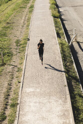 Sportive young woman running on a path - FMOF00403