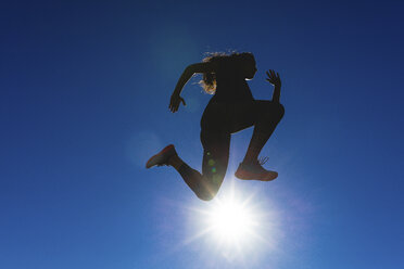 Sportive young woman jumping under blue sky in backlight - FMOF00406