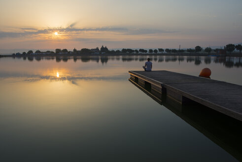 Relaxed girl on the floating platform on the lake at sunrise - SKCF00550