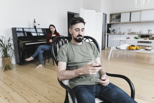 Couple at home, Man drinking wine, woman playing he piano in background - KMKF00581