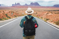 USA, Utah, Man with backpack standing on road to Monument Valley - KKAF02536