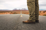 USA, Utah, Man standing on road to Monument Valley - KKAF02539