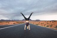 USA, Utah, Young man dong handstand on road to Monument Valley - KKAF02545