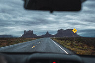 USA, Utah, Car driving to Monument Valley under a stormy sky - KKAF02548