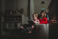 Mother with son reading book while sitting on armchair at home - CAVF50484