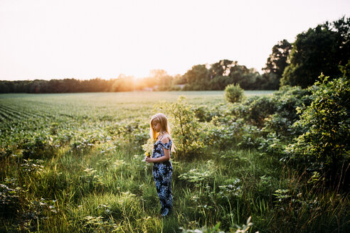 Side view of girl holding flowers while standing on grassy field against clear sky during sunset - CAVF50526