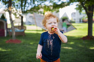 Cute baby boy eating ice cream while standing on grassy field at yard - CAVF50529